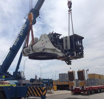 Big Construction Vehicle being moved by crane for road freight